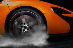 Orange Sport Car with detail on spinning and smoking wheels/tires doing burnouts Stock Images