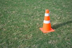 Orange sport cone. On green football field Stock Photos