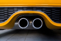Orange sports car exhaust pipe. Double car exhaust pipe detail in orange Royalty Free Stock Photos