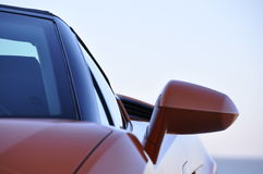 Orange sports car with mirror. An oranje sportcar in close-up with a mirror royalty free stock photo