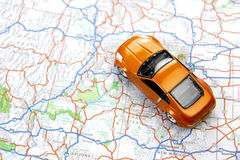 Orange sports car toy on map. Road trip concept Royalty Free Stock Photo