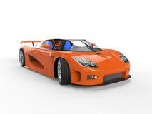 Orange sportscar med blåa platser Arkivbild