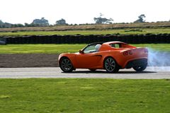 Orange sportscar on the track stock photos