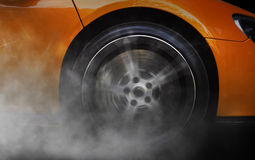 Orange Sportwagen mit Detail über die spinnenden und rauchenden Räder/die Reifen, die Burnouts tun Stockbild