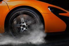 Orange Sportwagen mit Detail über die spinnenden und rauchenden Räder/die Reifen, die Burnouts tun Stockbilder