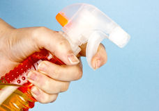 Orange spray bottle in hand Stock Images