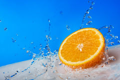 Orange in the spray water Stock Photos