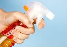 Orange Sprayflasche in der Hand Stockbilder