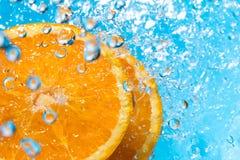Orange Spritzen im Wasser, Draufsicht Stockbilder