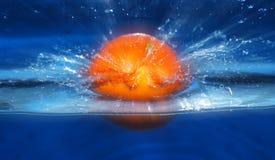 Orange Spritzen im Wasserblauhintergrund Stockfotos