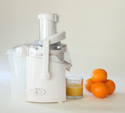 Orange squeezer or juicer. A studio view of a white orange squeezer or juicer with fresh squeezed orange juice and whole oranges nearby Royalty Free Stock Photography