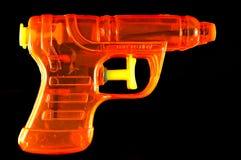 Orange Squirt Gun. Toy squirt gun isolated on a black mirrored background stock photos