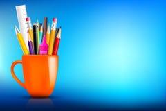 Orange stationary mug with pen pencil eraser marker on dark back Royalty Free Stock Images