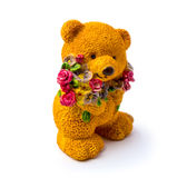 Orange statuette of a bear with flowers isolated on a white background. Photo of an orange statuette of a bear with flowers isolated on a white background stock image