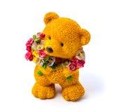 Orange statyett av en björn med blommor som isoleras på en vit bakgrund Arkivbilder