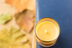 Orange stearinljus i den Glass hållaren på högen av bokmörker - blå marinbakgrund Torka gula röda Autumn Leaves Hemtrevlig nedgån arkivbild