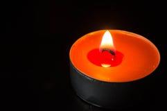 Orange stearinljusbränning på en svart bakgrund Royaltyfria Foton