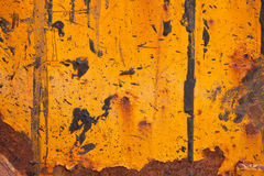 Orange steel with vertical tar stains. Fragment of an old industrial machinery stained with rust and tar Stock Images