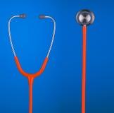 Orange Stethoskopkopfhörer und -glocke lokalisiert auf blauem Hintergrund Stockfoto