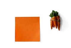 Orange sticky note and carrots bunch isolated Royalty Free Stock Photography