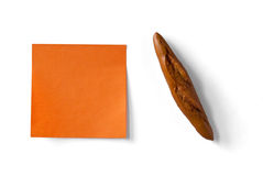 Orange sticky note and figure of french loaf Royalty Free Stock Photography