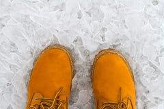 Orange Stiefel auf dem Eis Lizenzfreie Stockbilder