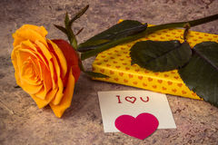 Orange stieg, das Geschenk, das im herzigen Papier bedeckt wurde und merkt ich liebe dich Stockfotos