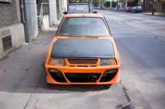 Orange stimmte das Auto ab, das auf dem Bürgersteig verlassen wurde Lizenzfreie Stockfotografie
