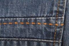 Orange stitch on jeans. As background stock image