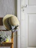 Orange stol, hatt och gammal lantbrukarhemdörr Arkivfoto