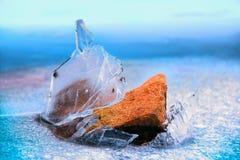 Orange stone breaks through the ice Stock Photo