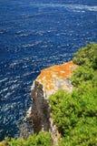 Orange stone in front the blue sea Stock Photo