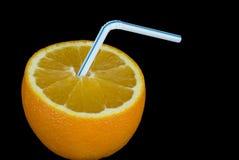 Orange with straw. An open ripe orange with drinking straw inside. Image on black studio background Stock Photography