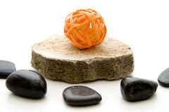 Orange straw sphere on stone Royalty Free Stock Images