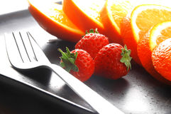 Orange & strawberries. On a plate on white background Stock Photo