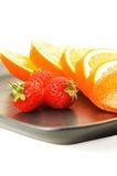 Orange & strawberries. On a plate on white background Stock Photography