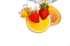 Orange and strawberries falling into water splash Royalty Free Stock Photos