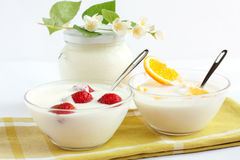 Orange and strawberry yogurt. Against the backdrop of a  jar of fresh yogurt Royalty Free Stock Photos