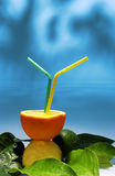 Orange with straws. On a blue background stock photography