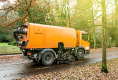 Orange street sweeper machine cleaning the street Stock Images