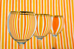 Orange stripe glass of water. Round glass of water infront orange and white striped background Stock Photos