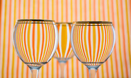 Orange stripe glass of water. Round glass of water infront orange and white striped background Stock Photo