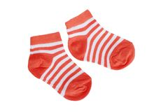 Orange striped baby socks on white background Stock Photos