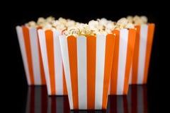Orange striped box with popcorn, black background Stock Photos