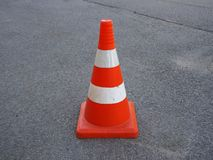 Orange striped traffic cone on an asphalt road. Red and white striped traffic cone on an asphalt road. It is used as a fence when carrying out road-building royalty free stock photos