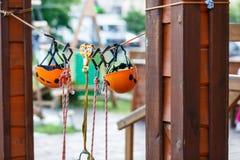 Orange Sturzhelme und Gurtung im Seilpark Erwachsener und Kinderausrüstung für das Klettern im Abenteuerseilpark Aktiver Lebensst stockbild