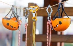 Orange Sturzhelme und Gurtung im Seilpark Erwachsener und Kinderausr?stung f?r das Klettern im Abenteuerseilpark Aktiver Lebensst lizenzfreie stockbilder