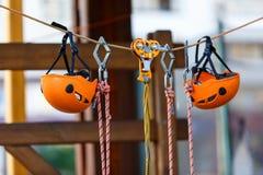 Orange Sturzhelme und Gurtung im Seilpark Erwachsener und Kinderausr?stung f?r das Klettern im Abenteuerseilpark Aktiver Lebensst stockfotografie