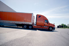 Orange stylish semi truck trailer unloading cargo in warehouse Stock Photos
