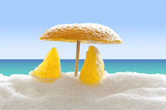 Orange on the sugar beach. Two orange pieces under orange umbrella on the sugar beach Stock Photos